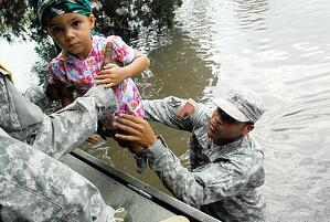 U.S. Army Sgt. Lee Savoy lifts a child into a boat for evacuation from a flood caused by Hurricane Isaac in La Place, La. in 2012.