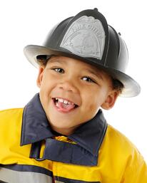 """Closeup image of an adorable preschool """"Fire Chief"""" in his helmet and yellow coat. On a white background."""