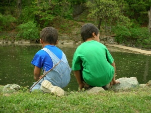 children next to pond outside
