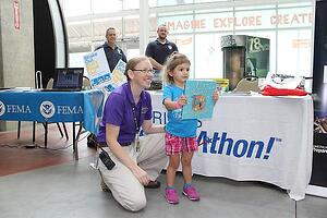 Kansas City, Mo. -- Science City Educator Heather Edvenson, gives Anna Thompson of Leavenworth, Kan., a book, as a prize for participating in their Shakeout earthquake drill at Science City (inside Union Station), Sat., Aug. 22, 2015. The drill was part of an America's PrepareAthon event. FEMA photo Amanda Bicknell