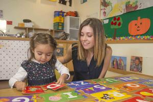 teacher helps girl with alphabet puzzle