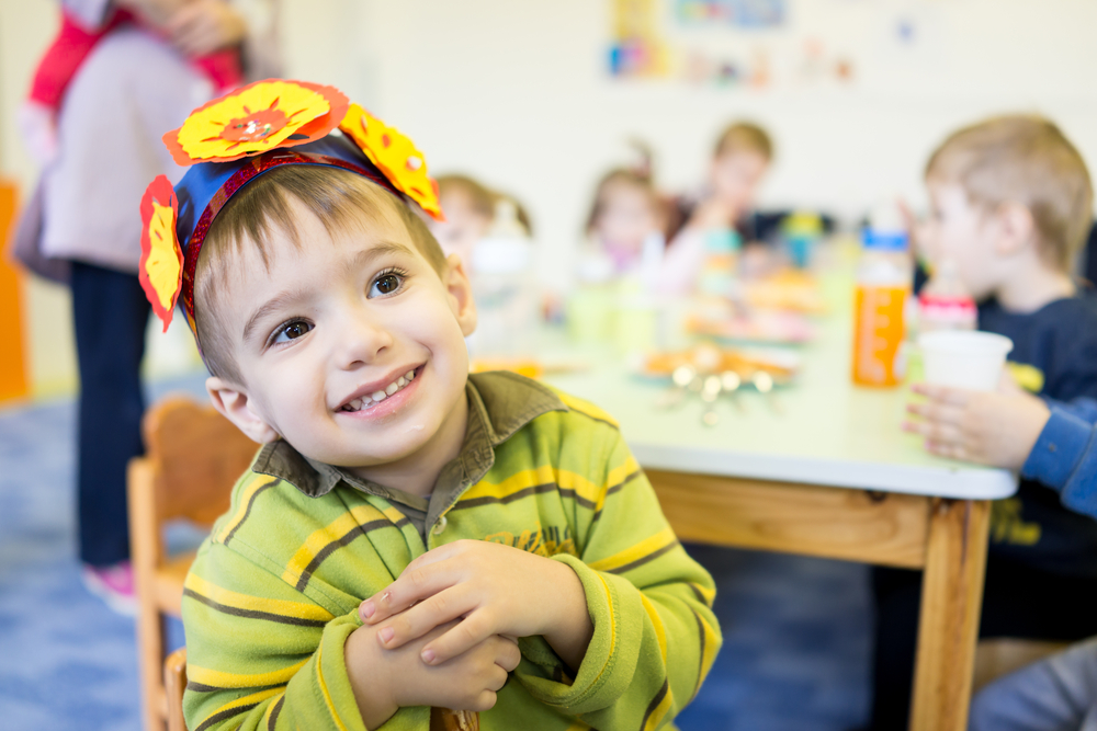 young boy eats with his friends at a child care program