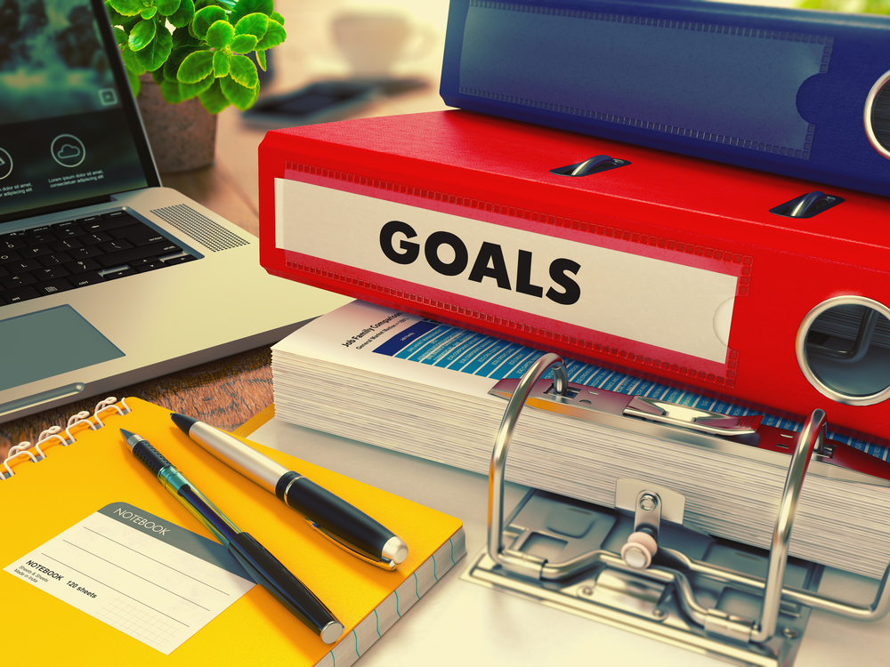 Red Office Folder with Inscription Goals on Office Desktop with Office Supplies and Modern Laptop