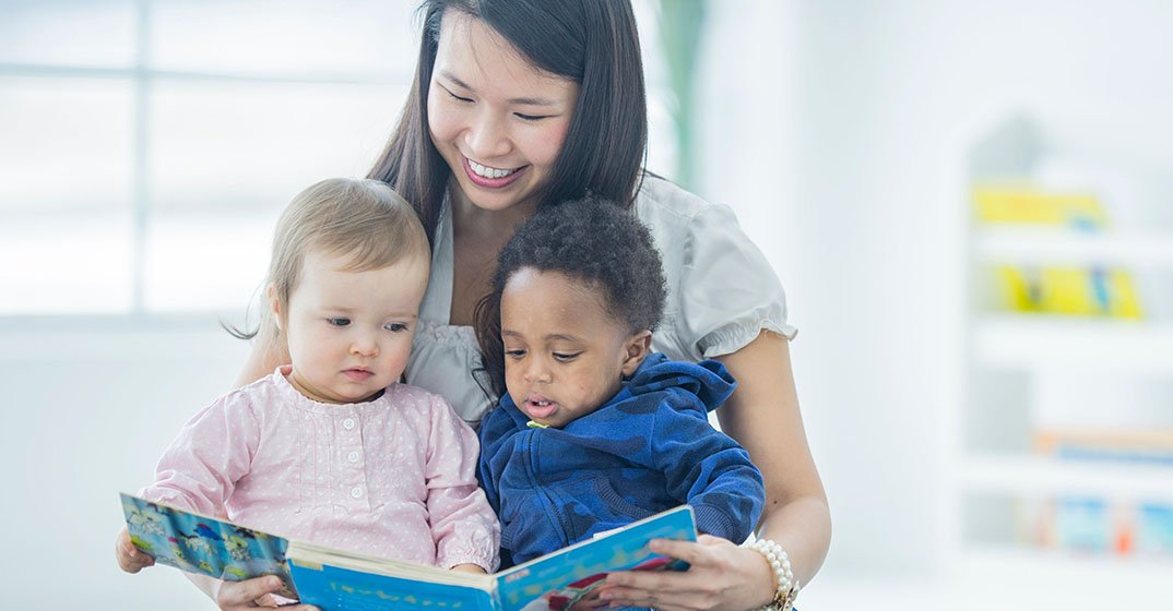 Provider reads a book to two toddlers.