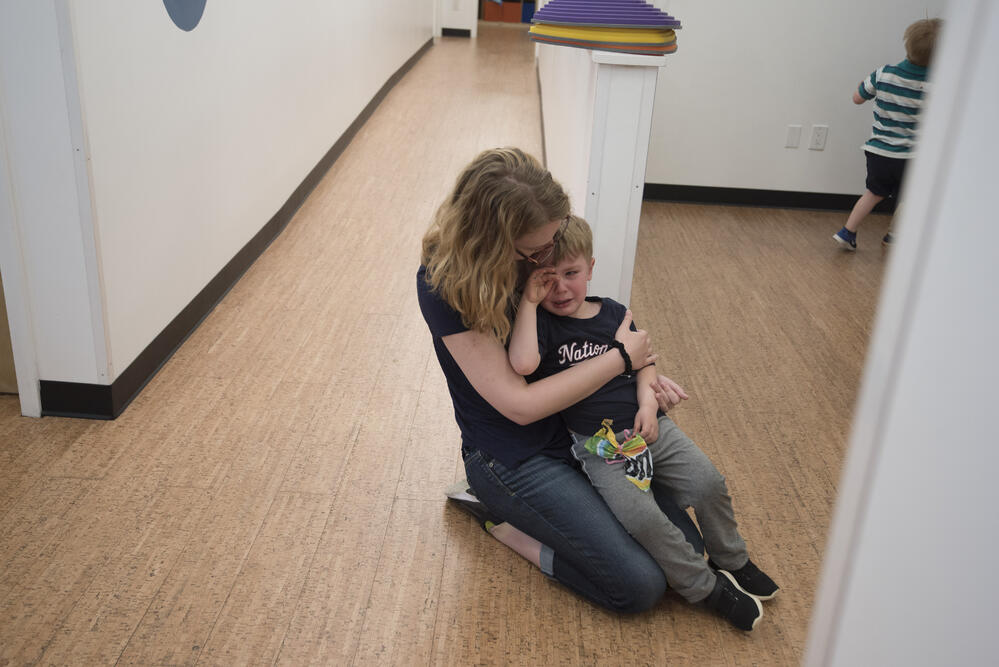 a teacher consoles a crying student