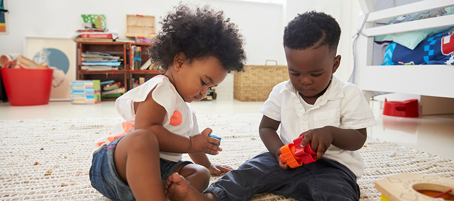 baby-boy-and-girl-playing-with-toys-in-playroom-to-PCPWKX2 (1)