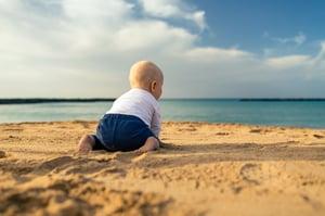 baby-boy-playing-on-a-beach-EPRXUQN