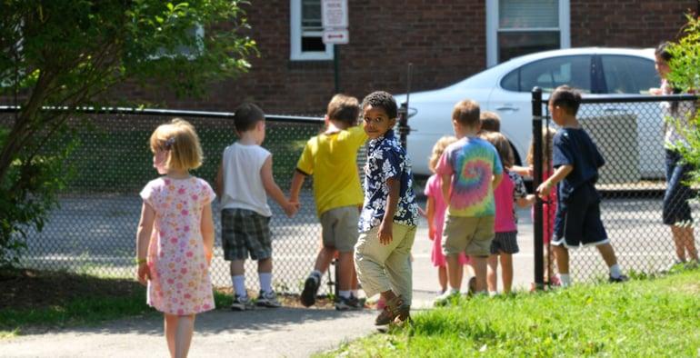 boy outside preschool looks toward camera before covid-19