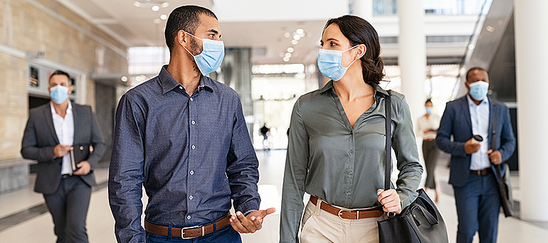 colleagues wearing covid-19 masks talking with each other