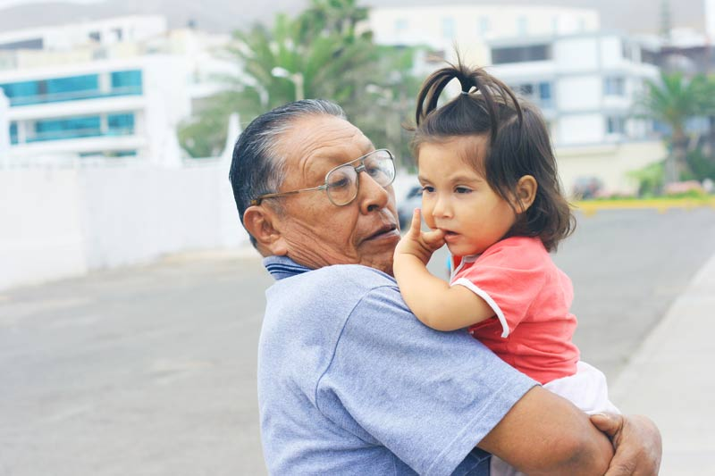 Grandfather holds toddler girl
