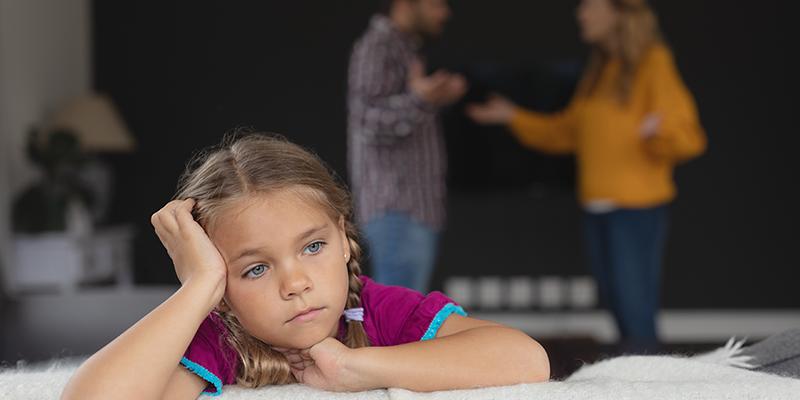 sad-girl-leaning-on-sofa-while-caucasian-parents-YMZNTAU
