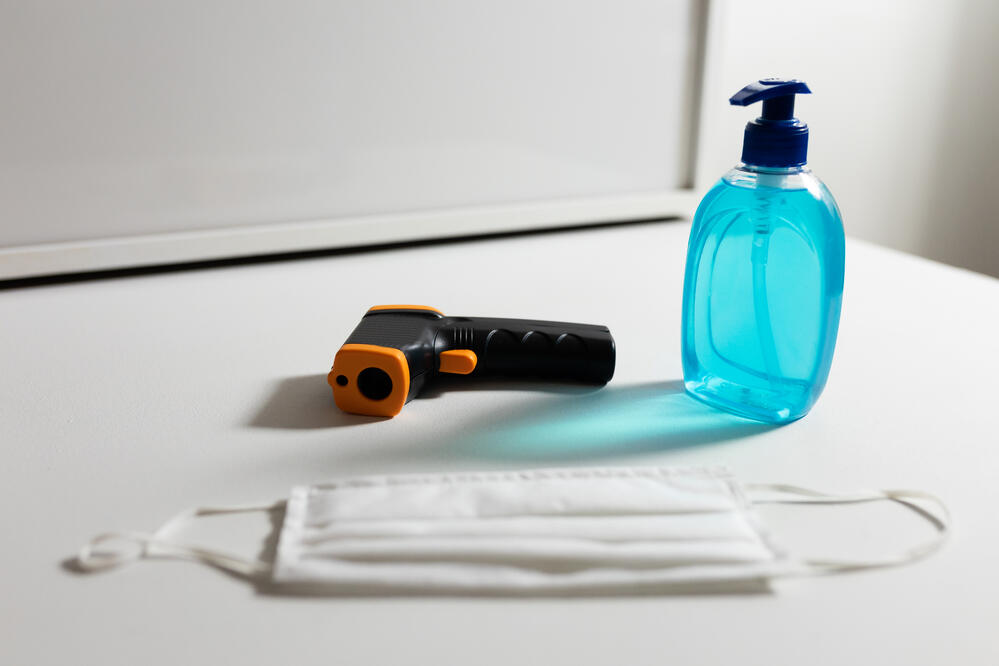 a thermometer, face mask and hand sanitizer
