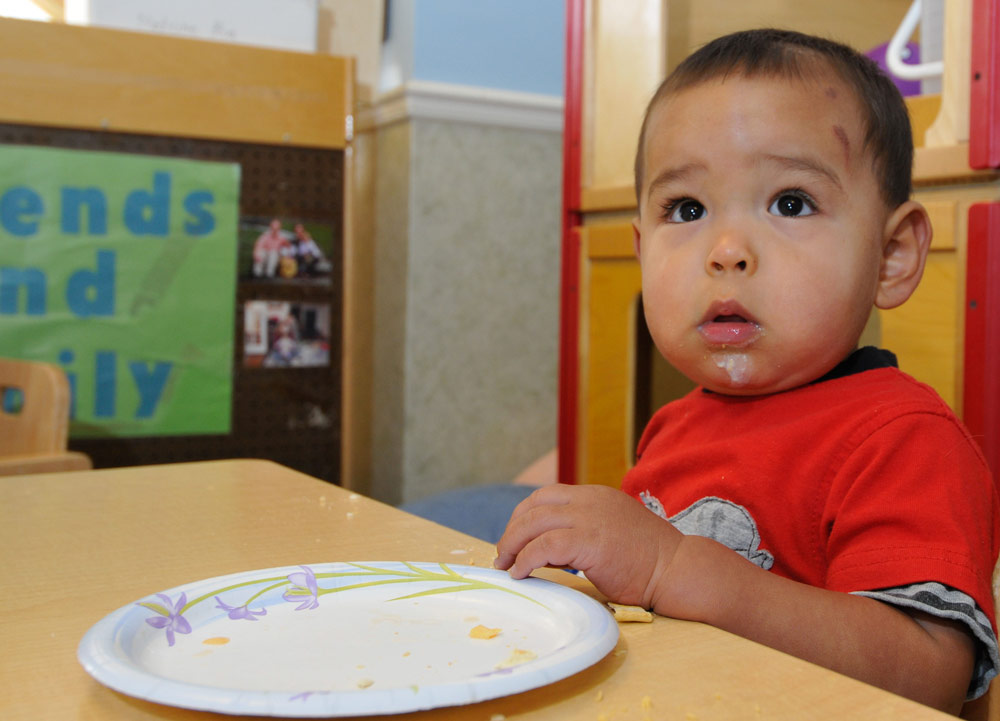 A toddler eats in a child care center