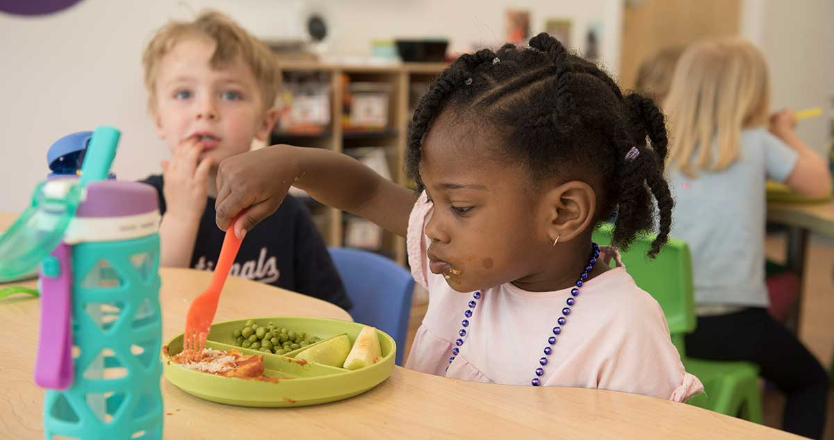 young girl eats lunch at table